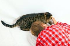 Boy cuddles his tabby cat Royalty Free Stock Photos