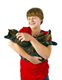 Boy cuddles his tabby cat Stock Photo