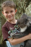 Boy cuddling Koala. Wildlife parks in Australia offer visitors an opportunity to cuddle a koala. Eight year old boy cuddles in this image stock photography