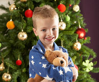 Boy Cuddling Teddy Bear In Front Of Christmas Tree Royalty Free Stock Images