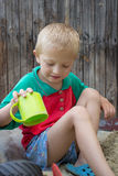 Boy with a cup of sand Stock Images