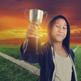 Boy with a cup and sun set at corner soccer filed Stock Image