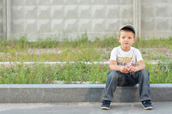 Boy on a curb Stock Photos