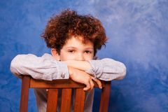 Boy with curly hair sits backwards on wooden chair. Portrait of cute boy with curly hair sitting backwards on wooden chair against blue background and looking at Royalty Free Stock Photos