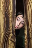 Boy and the curtain. A boy looks out from behind the curtain Stock Image