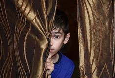 The boy and the curtain. The boy looks out from behind the curtain Royalty Free Stock Image