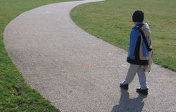 Boy on Curved Path. Boy on Curved Stone Chip Path on Grass Lawn in Park stock image