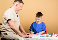 Boy cute child and his father doctor. Hospital worker. First aid. Medical help. Trauma and injurie. Medicine concept. Kid little doctor sit table medical tools royalty free stock photography