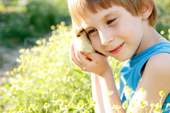 Boy cute hugs chiken in hand nature summer Stock Image