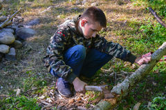 Boy cuts firewood. The boy cuts firewood in forest stock images