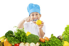 Boy cuts lemon and vegetables Royalty Free Stock Images
