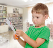 Boy cuts paper with scissors Royalty Free Stock Photos