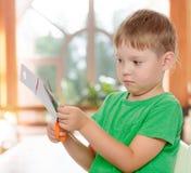 Boy cuts with scissors cardboard Stock Photos