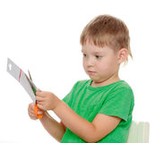 Boy cuts with scissors cardboard Stock Images