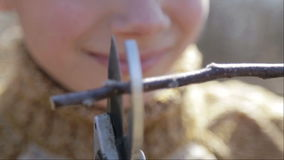 The boy cuts the trees in the garden with a pruner. The child helps to trim the trees in the park in the spring. stock video footage