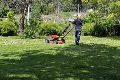 Boy cutting grass. With a lawn mover Stock Photos