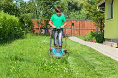 Boy cutting grass around the house in summertime. Focusing on the operation royalty free stock photo