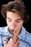 Boy cutting his nose. Boy cutting his hair in black background stock photo