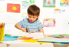 Boy cutting paper with scissors. 3 years old boy cutting cardboard paper with scissors in preschool art class Stock Images