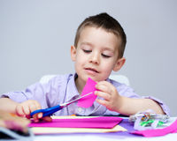 Boy is cutting paper using scissors royalty free stock photos