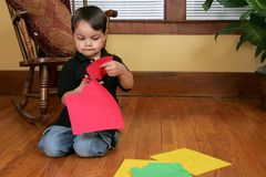 Boy cutting up paper Royalty Free Stock Images