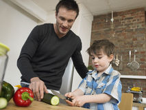 Boy Cutting Vegetable While Father Looking At It Stock Photos