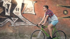 Boy cycles near graffiti wall. Attractive boy cycling near graffiti wall, wearing glasses and checked red shirt on the back, outdoor slowmotion stock video footage