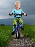 Boy cycling. On a dirt road Stock Photo