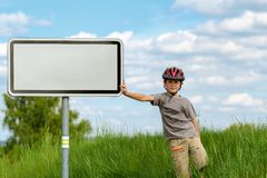 Boy cyclist leaning on blank sign Stock Photos