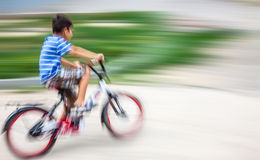 Boy cyclist in traffic on the city roadway. Royalty Free Stock Image
