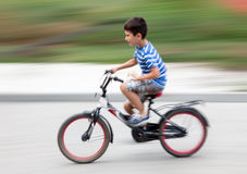 Boy cyclist in traffic on the city roadway. Stock Photography