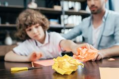 Boy and dad with crumpled. Colorful paper stock images