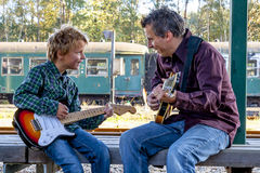 Boy and dad with guitars. Boy and his dad playing guitar at an old rail road station Stock Photo