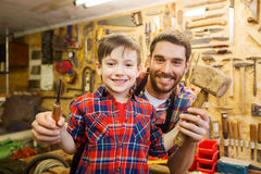 Boy with dad holding chisel and hammer at workshop Royalty Free Stock Photo