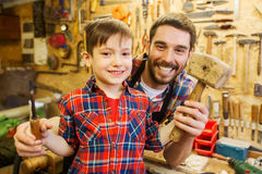 Boy with dad holding chisel and hammer at workshop. Family, carpentry, woodwork and people concept - happy father and little son with hammer and chisel working stock images