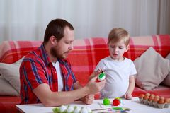 Boy and dad paint eggs stock images