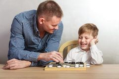 Boy with dad playing checkers at home stock photos