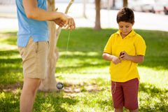 Boy and dad playing with a yo-yo. Cute kid learning how to play with a yo-yo with his father Royalty Free Stock Image