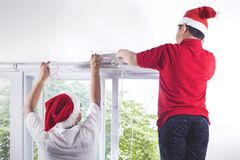 Boy and dad put Christmas light on wall Royalty Free Stock Photography