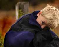Boy in Dad's Coat. Boy snuggles inside Dad's coat Stock Images