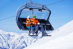 Boy and dad sit in chair lifting on the mountain Stock Photo