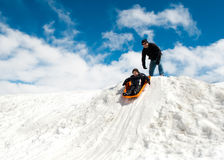 Boy and dad sledding in winter Stock Photo