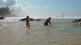Boy with daddy rests in ocean at tropical resort slow motion