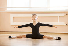 Boy dancer doing splits while warming up. At ballet dance class stock image