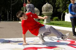 Boy dances breakdance on the street in front spectators. hip hop dancer