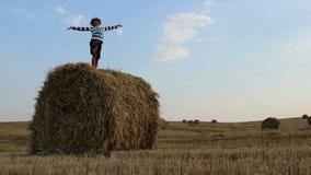 Boy dancing on a haystack in a field stock footage