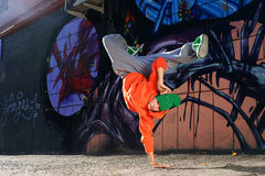 Boy dancing on the street graffity wall. Teenager dancer orange jacket green cap Royalty Free Stock Image