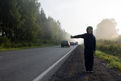 The boy at the road hitchhiking. A boy in a dark hooded sweatshirt hitchhiking on a forest road in a fog Stock Photo