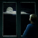 Boy in the dark window looking at the bright full moon Royalty Free Stock Image