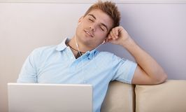 Boy daydreaming with earphones Royalty Free Stock Photography